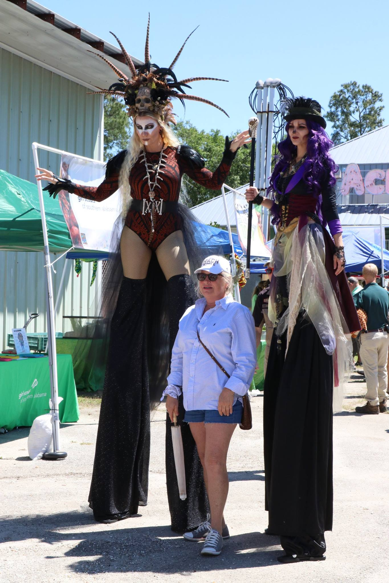 woman standing by stilt walkers