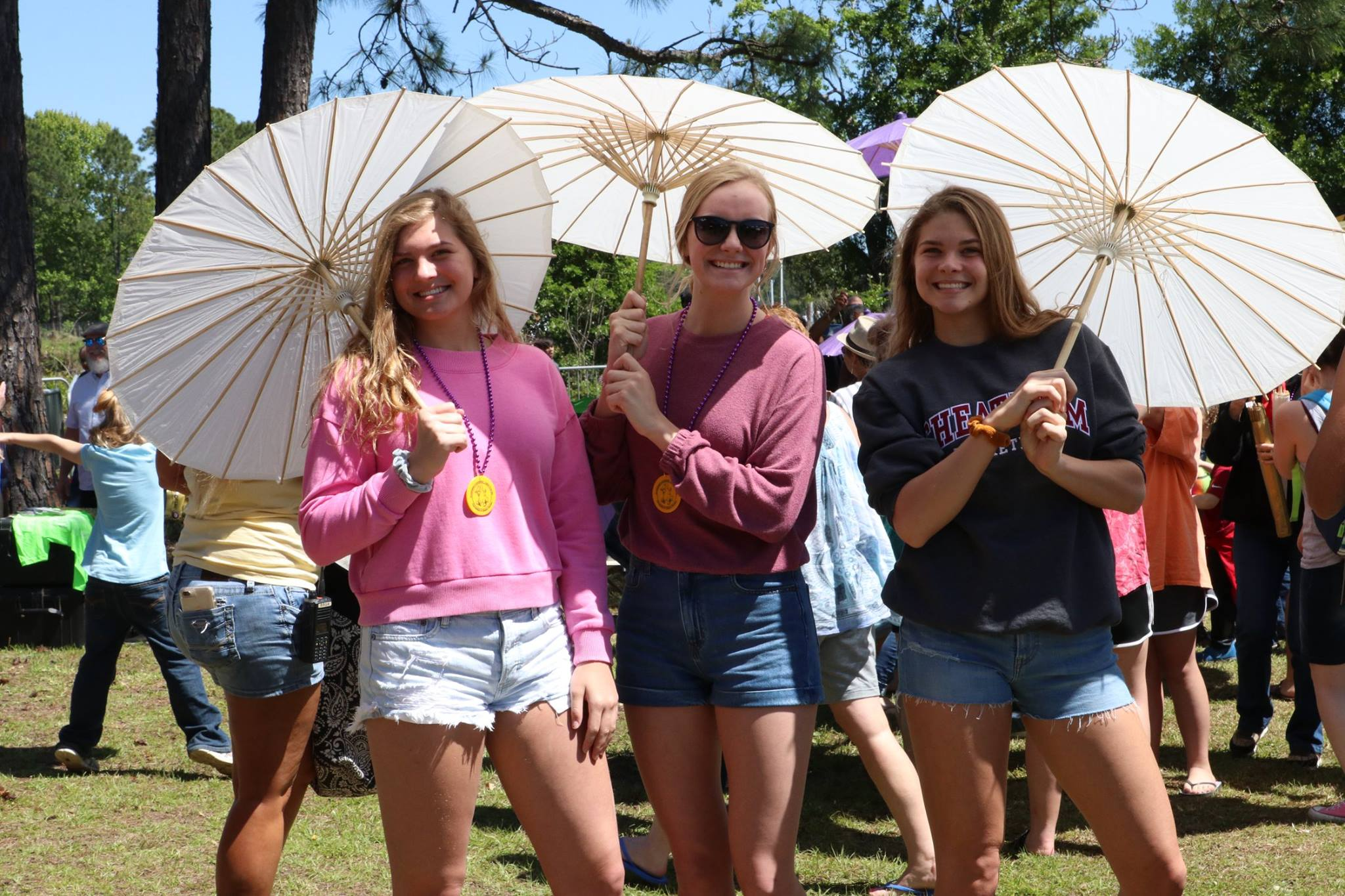 three girls holding zydeco umbrellas